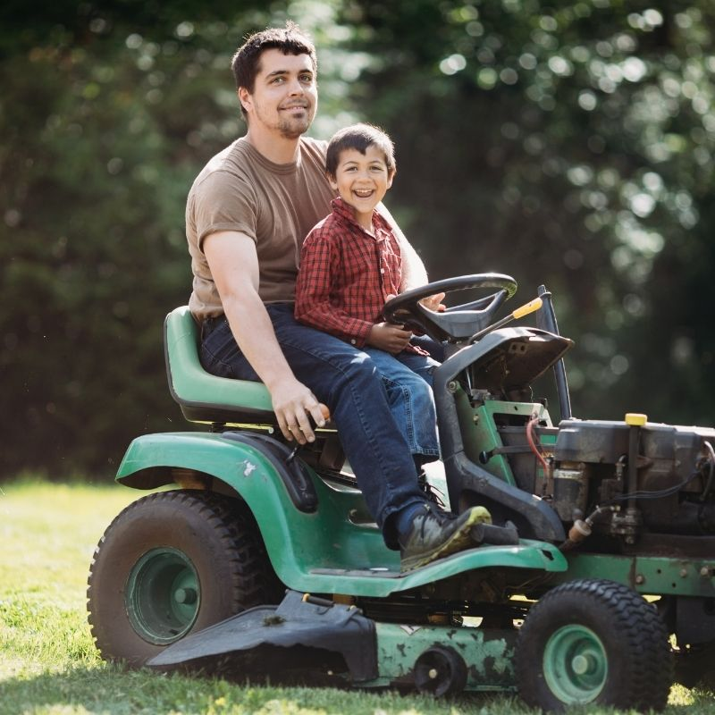 Father and son on riding lawn mower