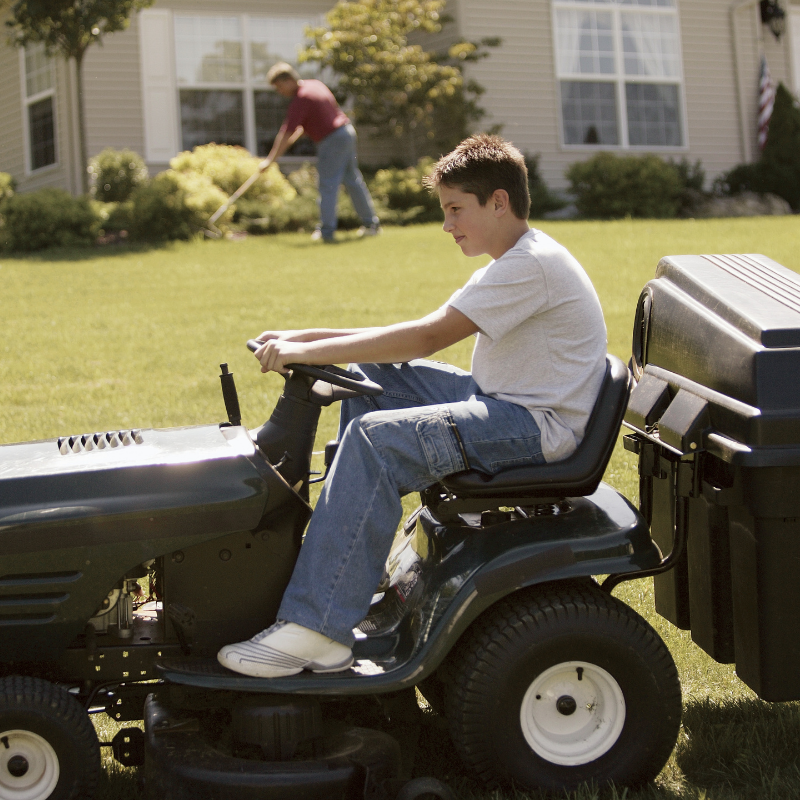 Teenager mowing lawn